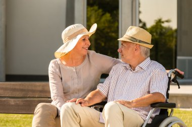 Senior disabled man and wife talking outdoors