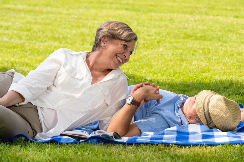 Elderly couple enjoying relax time in sunny park