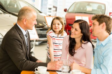 Car dealer and couple doing paperwork