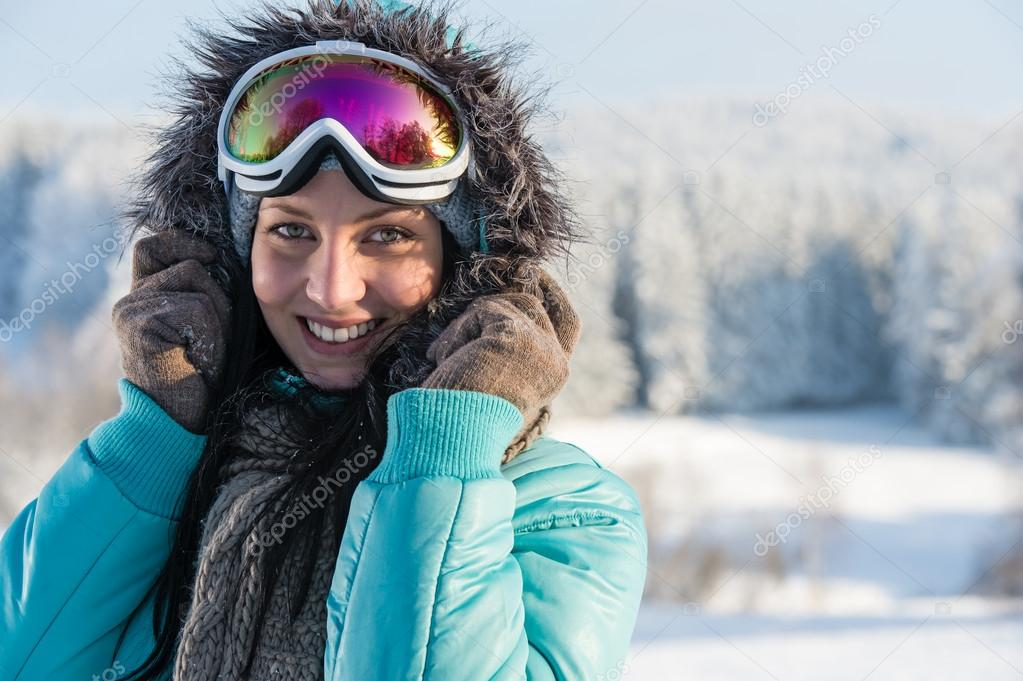 Portrait of young woman in grey fur snow winter mountains