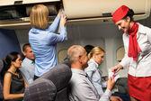 Fotografia Air hostess controllo biglietto aereo cabina sorridente
