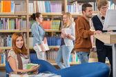 Lächelnder Student in Bibliothek mit Freunden
