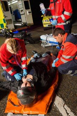 Sağlık görevlileri yaralanan motosiklet sürücüsü inceleniyor