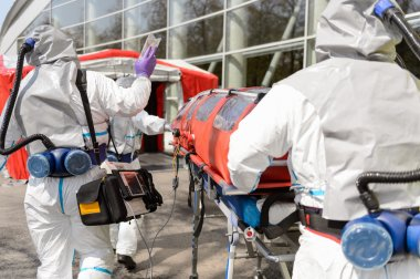 Hazardous material team pushing stretcher towards decontamination chamber stock vector