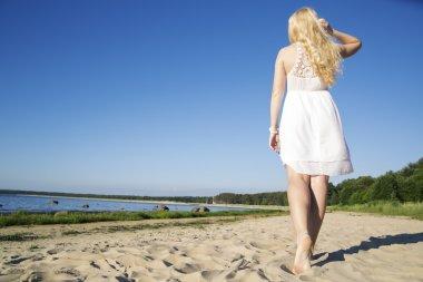 Woman in white dress walking at beach