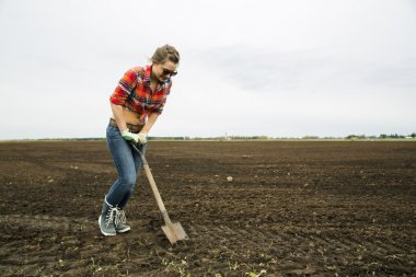 Woman with sharp shovel try dig ground