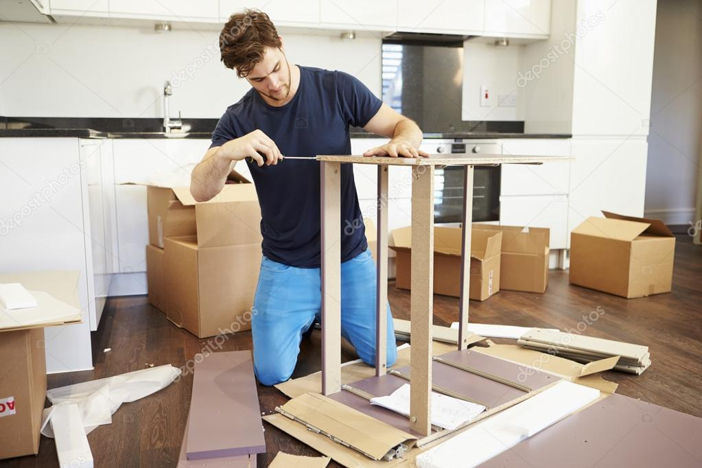 Man putting together assembly furniture stock photo for I furniture assembly