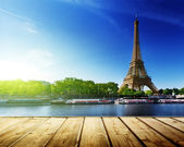 Photo background with wooden deck table and Eiffel tower in Paris