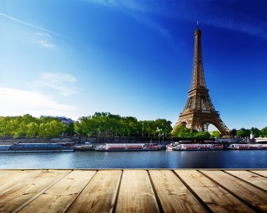 background with wooden deck table and Eiffel tower in Paris