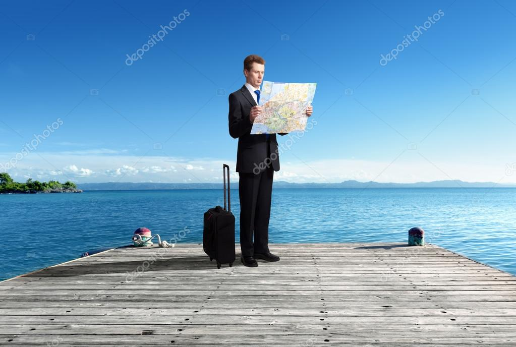 Business man standing on pier whith map in hands