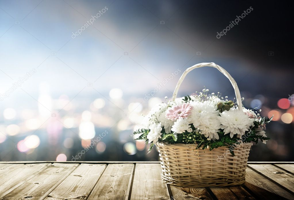 flowers in basket and lights of night city