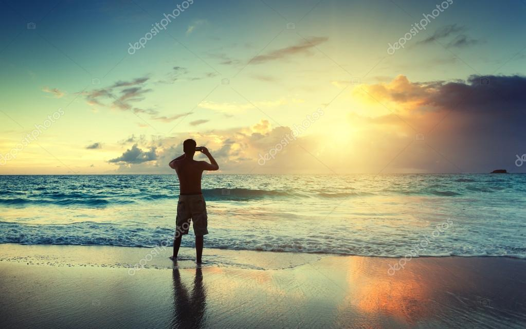 Young man on the beach take photo on mobile phone