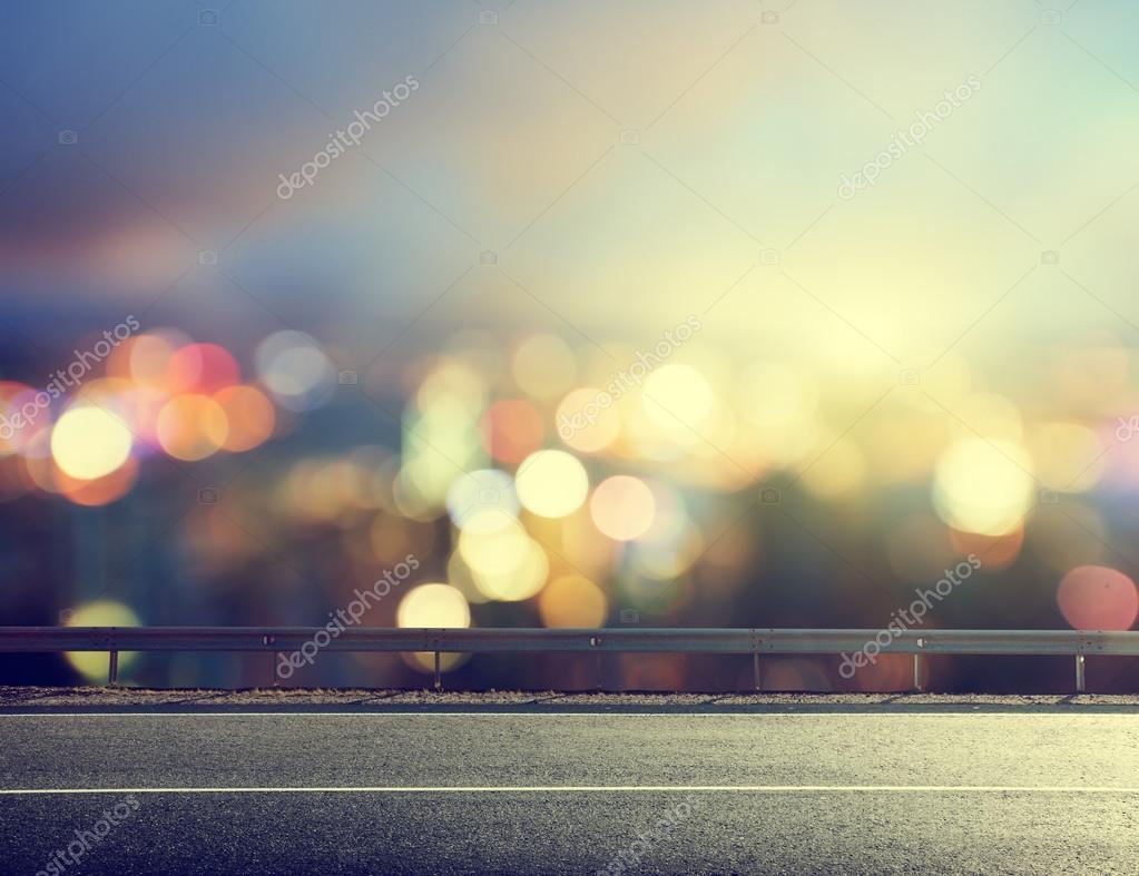 Asphalt road and blurred modern city