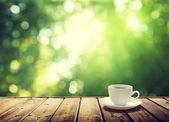 šálek kávy a slunné stromy pozadí