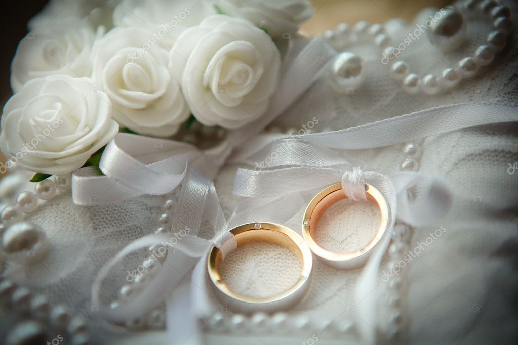 Two wedding rings with white flower in the background.