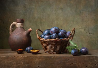 Still life with black plums in a basket