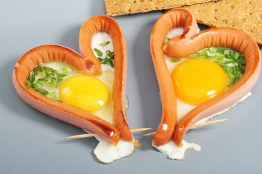 Two sausages in a heart-shaped fried eggs.