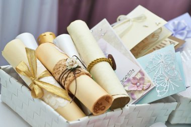 Wedding invitation scrolls in the bucket