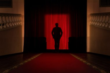 Male silhouette over red curtain background