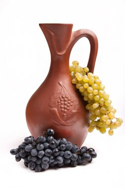 traditional clay jug for wine with bunch grapes