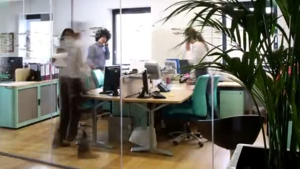 Attractive young professionals at work in busy modern office