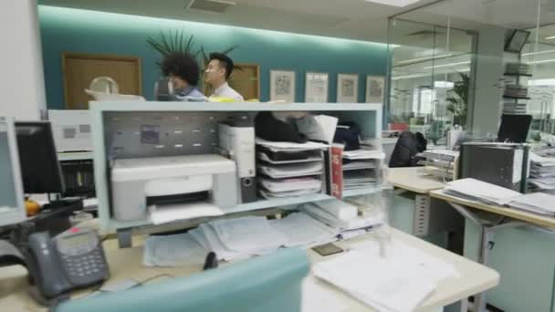 Two young business men talking together as they walk around the office