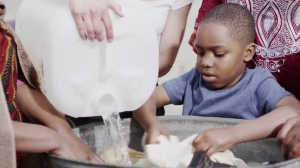 African family and community members work together, washing clothes by hand