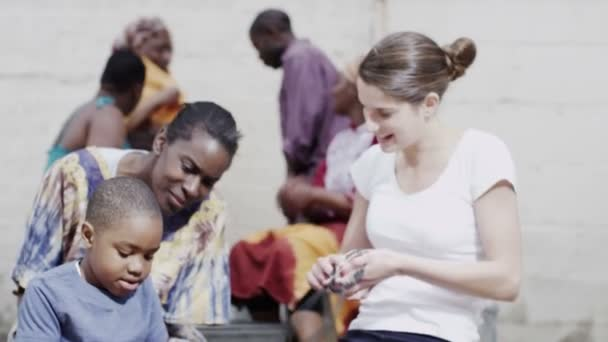 Medical worker from charity organisation uses stethoscope to examine a small boy