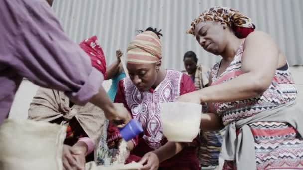 African family working together, measuring out quantities of rice or grain