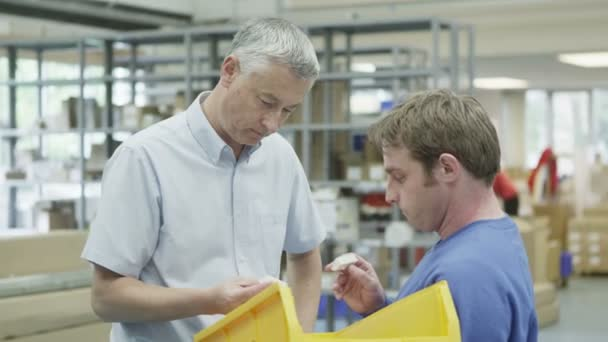 Cheerful factory or warehouse worker taking instruction from the foreman