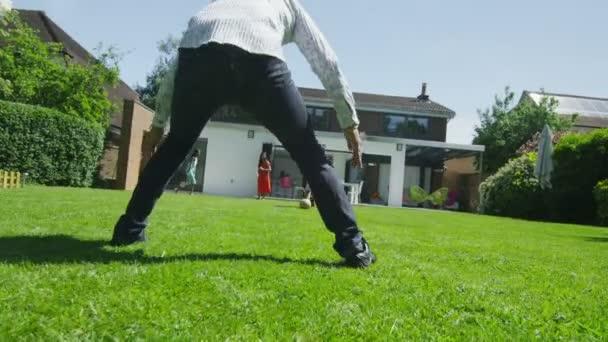 roztomilý mladý chlapec sportu se svým otcem, v zahradě na letní den