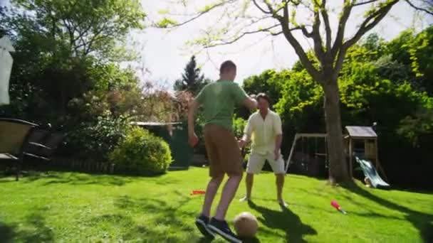 Young boy playing soccer with his father outdoors on a sunny day