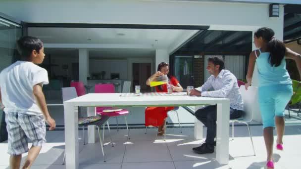 rodina asijských pití šťávy na terase jejich moderní domov za slunečného dne