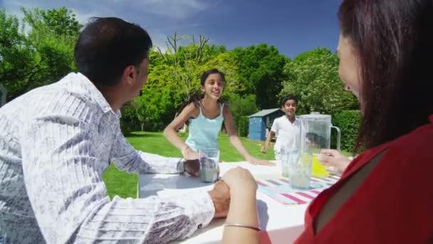 asiatische Familie trinken Saft auf Terrasse ihres modernen Hauses an einem sonnigen Tag