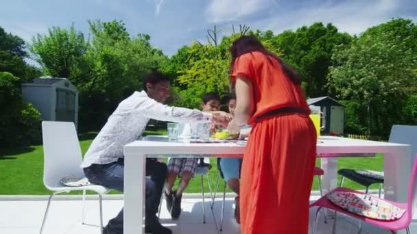 asijské rodina jíst oběd na terase v jejich zahradě