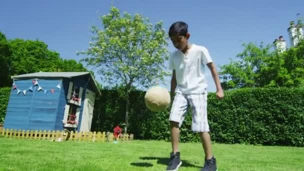 aranyos fiatal fiú az apjával, a kertben egy nyári napon sportolás