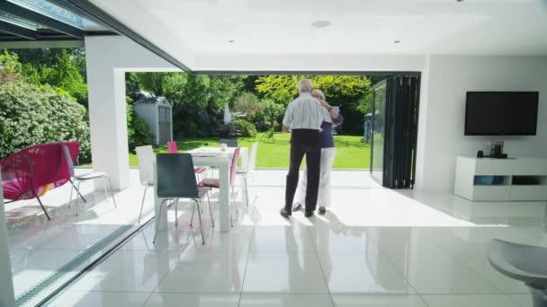 romantický starší pár spolu tančit ve dveřích své moderní domov