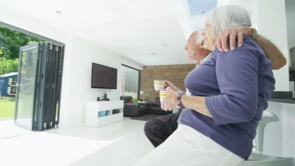 romantický důchodci pár objetí a podívejte se na jejich zahradě na letní den