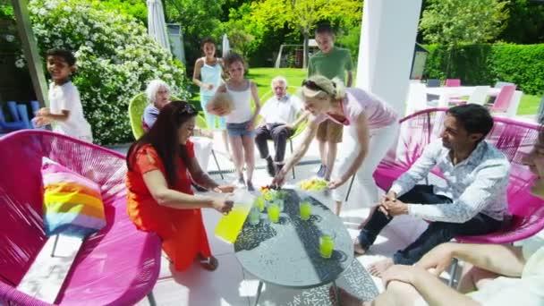 různorodá skupina rodina a přátelé si občerstvení v zahradě za slunečného dne
