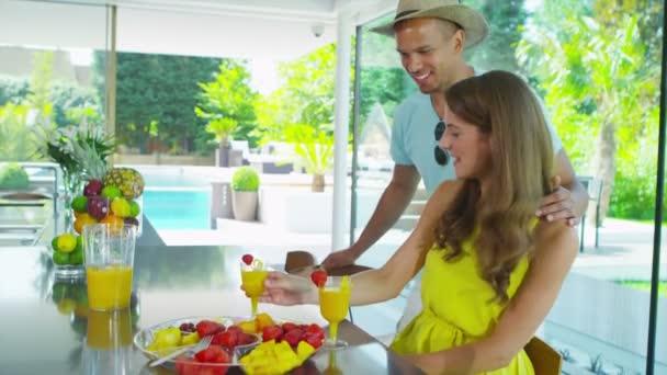 šťastný mladý pár pití šťávy zdravé nápoje v kuchyni moderní domov