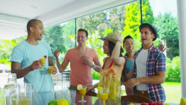 Happy group of friends drinking healthy juice drinks in kitchen of modern home