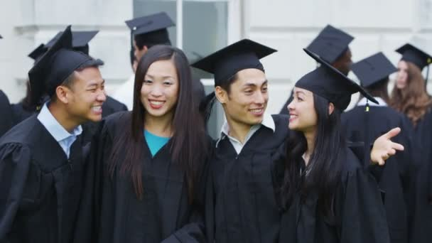 Asian student friends outdoors on graduation day