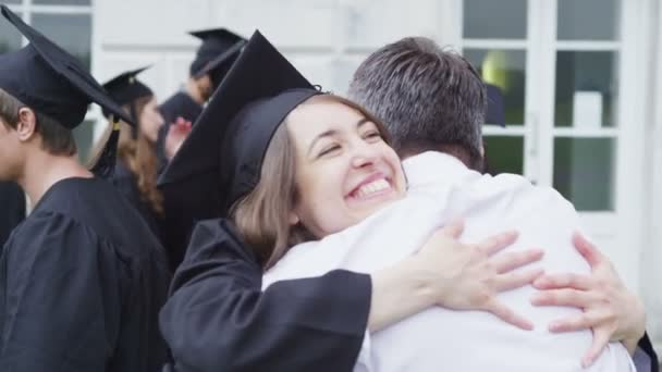 Students on graduation day are congratulated by parents