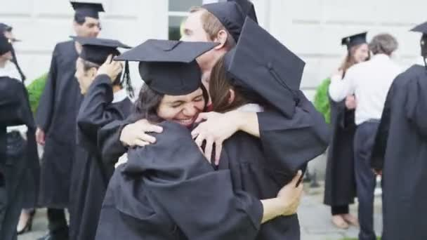 Student friends hugging each other on graduation day