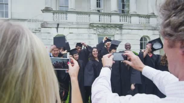 Student friends on graduation day standing outdoors