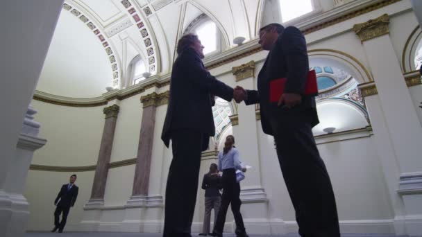 Two men talk and shake hands