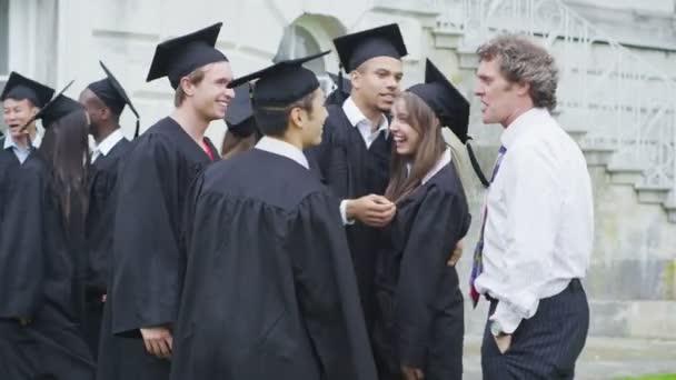 studentské přátelé objímání navzájem v den promoce