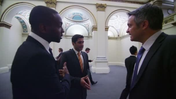 Three men talk and shake hands