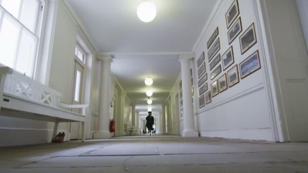 studenti na maturitní den běží přes chodbu