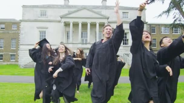 Graduates run and throw their caps